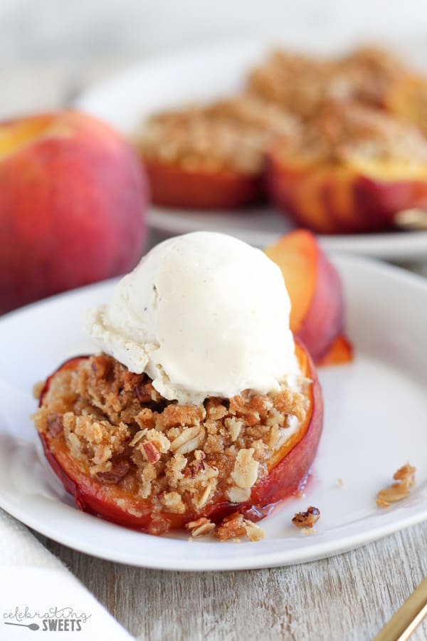 Half of a Baked Peach Stuffed with Pecan Streusel, topped with Vanilla Ice Cream.