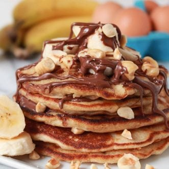 Stack of pancakes topped with banana, chocolate and nuts.