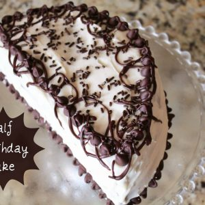Half birthday cake on a glass plate.