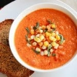 Tomato soup in a white bowl topped with corn.