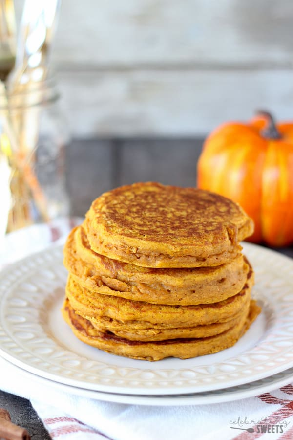 Stack of pumpkin pancakes on a white plate with a pumpkin in the background.