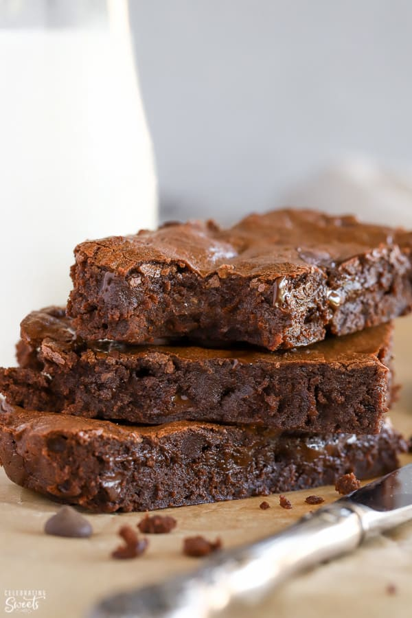 Stack of 3 brownies with a glass of milk in the background.