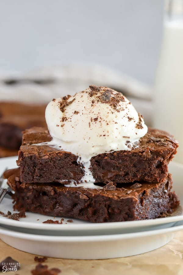 Two brownies on a white plate topped with vanilla ice cream.