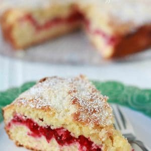 Slice of cranberry cake on a green and white plate.