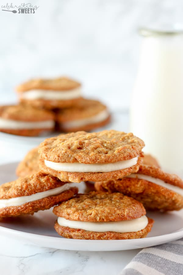Carrot cake cookies filled with frosting on a white plate.