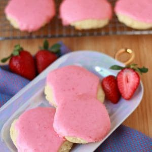 Sugar cookies covered with pink frosting on a purple plate.