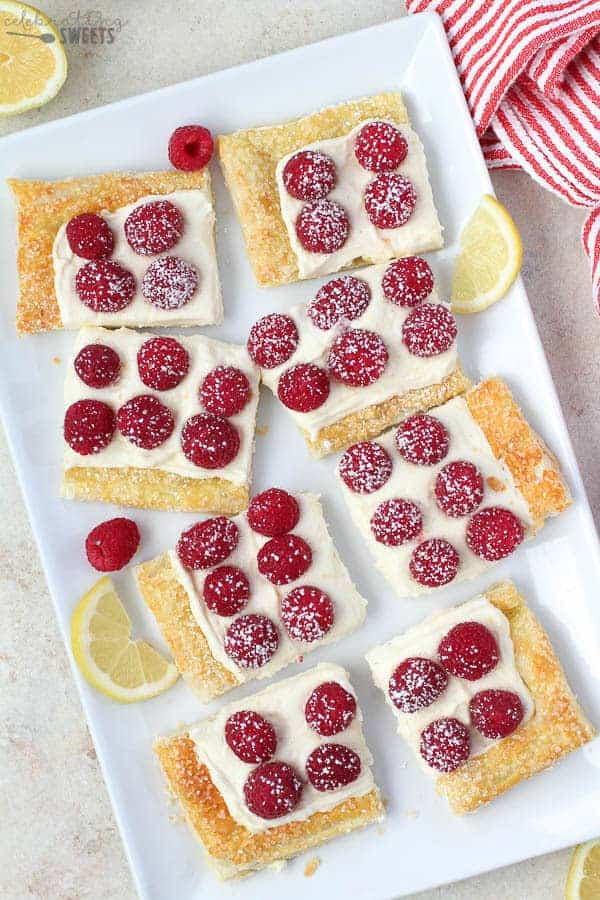 Slices of Lemon Tart topped with Raspberries on a White Platter.