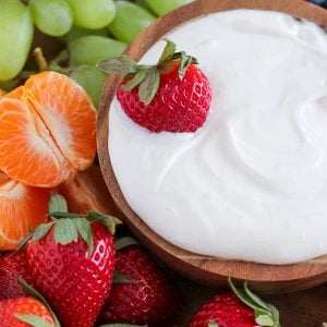 Bowl of dip with fruit around it.