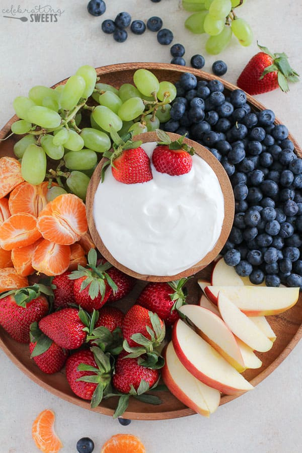 Platter of fruit with a bowl of dip in the center.