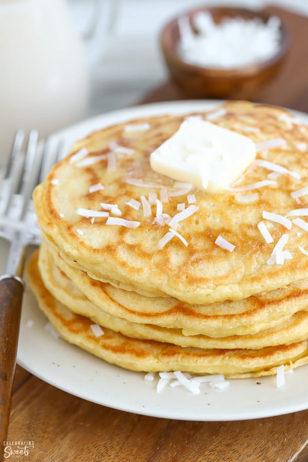 A stack of coconut pancakes topped with butter and shredded coconut.