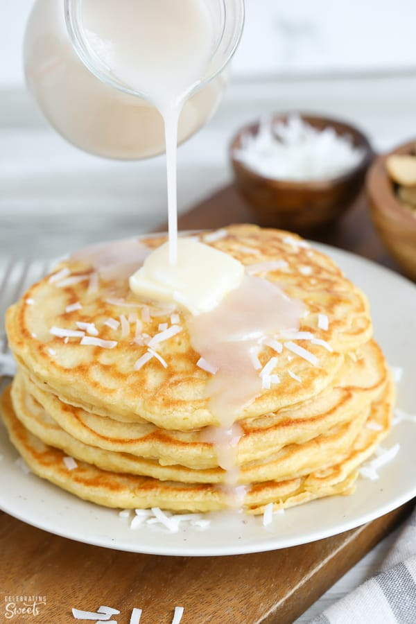 Coconut syrup poured over a stack of coconut pancakes.