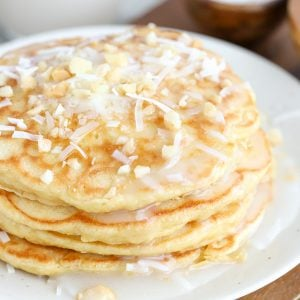 Stack of coconut pancakes topped with coconut syrup, shredded coconut and macadamia nuts.