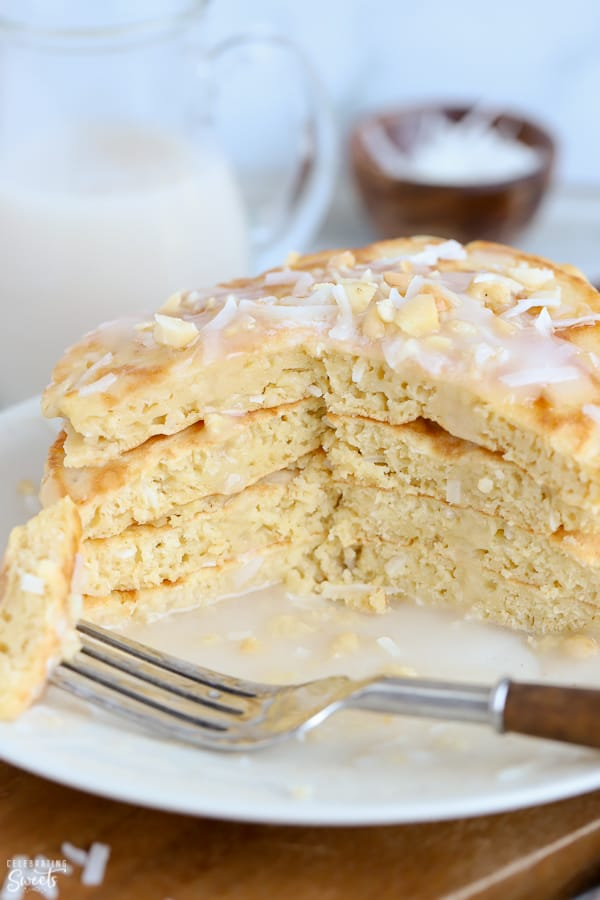 Stack of coconut pancakes on a white plate with a fork.