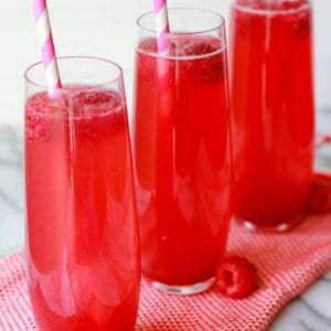 Three thin glasses filled with a pink beverage.