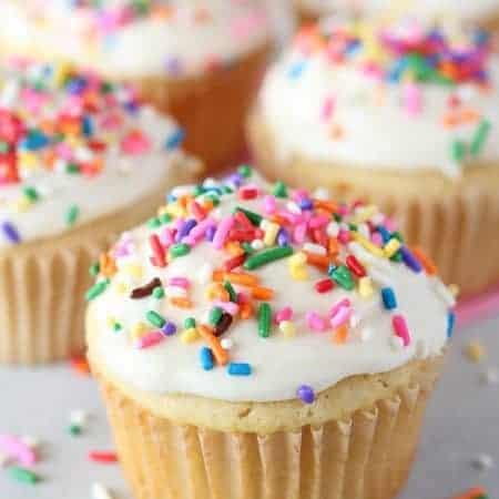 Vanilla cupcakes with vanilla ice cream and rainbow sprinkles.