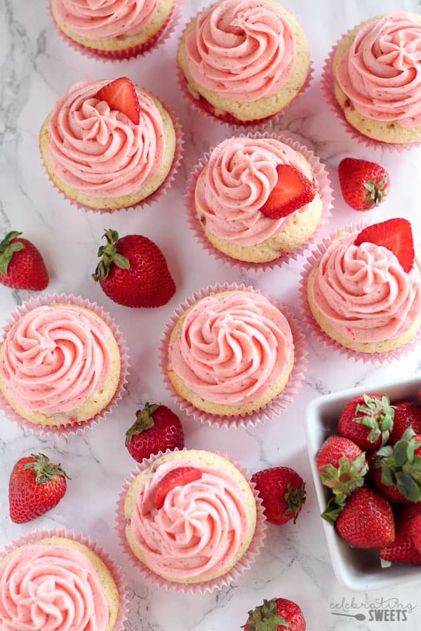 Overhead of strawberry cupcakes with pink frosting.