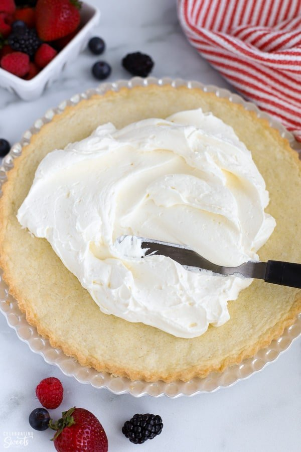 Whipped cream frosting being spread onto a sugar cookie crust.