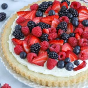 Fruit tart topped with red and blue berries on a white plate.