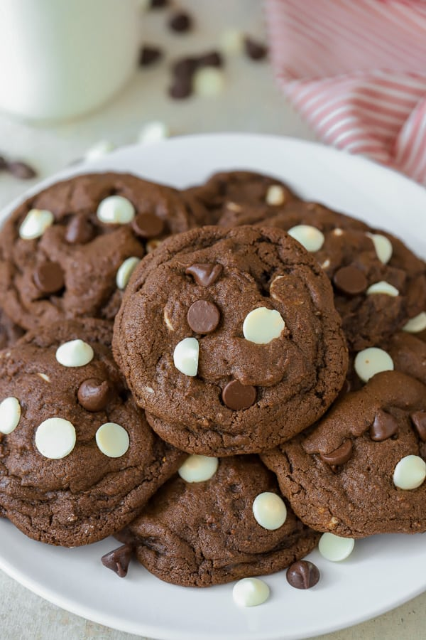 White plate filled with chocolate cookies filled with white chocolate chips.