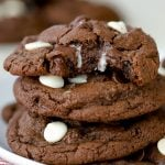 Three chocolate cookies stacked on a white plate.