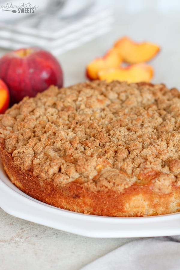 Peach crumb cake with peaches in the background.