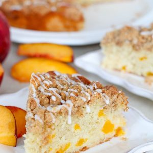 Slice of peach cake on a plate with fresh peaches.