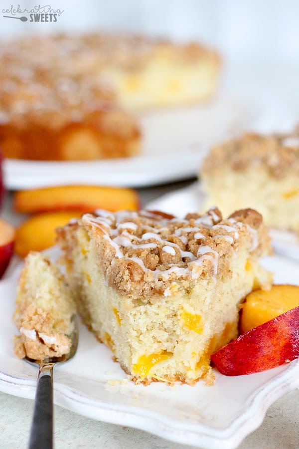 Slice of peach cake on a white plate with slices of peaches.