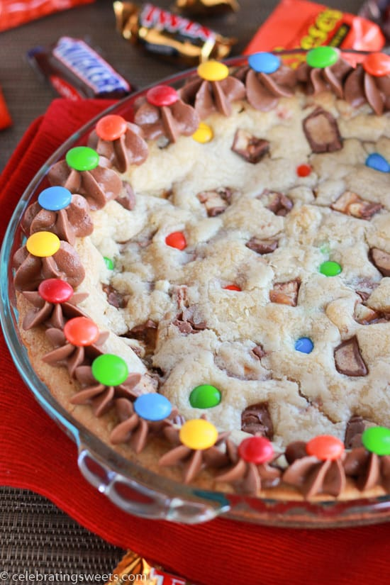 Cookie cake filled with candy bars and topped with chocolate frosting.