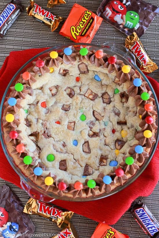 Cookie cake topped with M&M\'s candies and chocolate frosting.