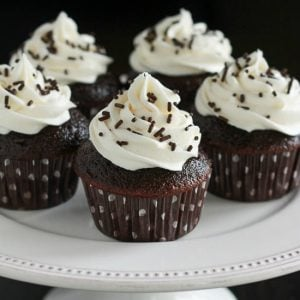 Chocolate cupcakes topped with vanilla frosting and chocolate sprinkles on a white platter.