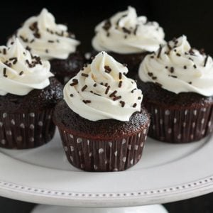 Five chocolate cupcakes topped with vanilla frosting.