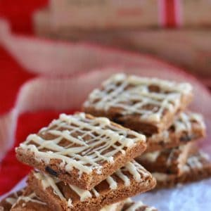 Stacks of gingerbread bars drizzled with icing on a piece of parchment paper.