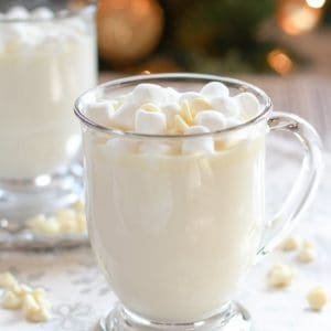 Glass mug filled with white hot chocolate.