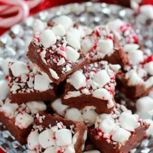Slices of fudge on a silver plate topped marshmallows and crushed candy canes.
