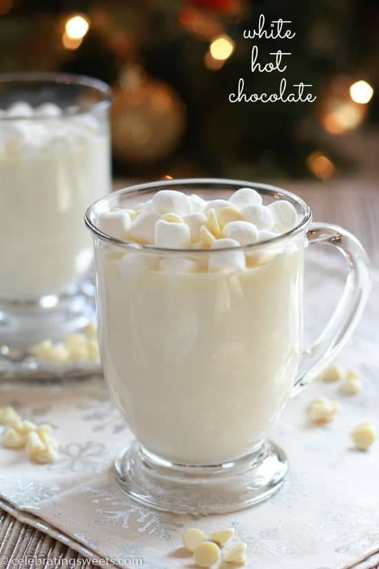 A close up of a glass cup on a table filled with white hot chocolate.