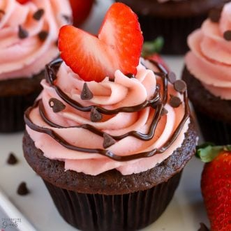 Chocolate cupcake topped with strawberry frosting and a heart shaped strawberry.