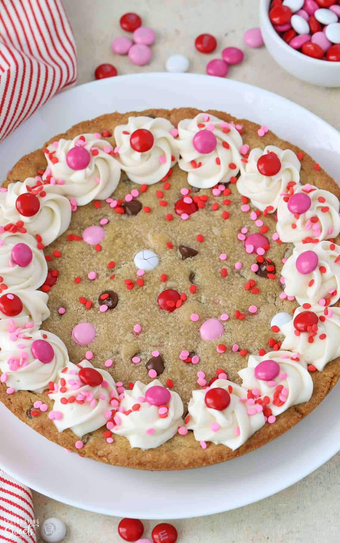 Cookie cake topped with frosting and red and pink M&M's