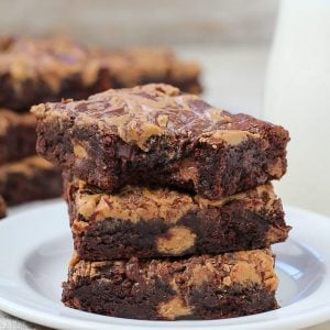 Stack of three peanut brownies on a plate.