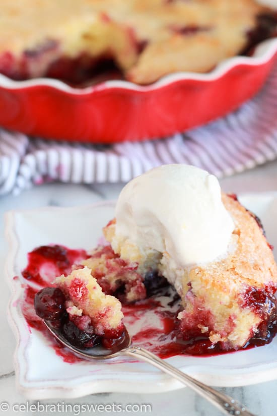 Berries topped with cake and a scoop of ice cream on a white plate.