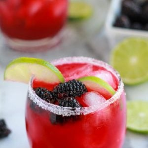 Blackberry margarita garnished with lime.