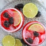 Blackberry margaritas in glasses garnished with lime slices and blackberries.