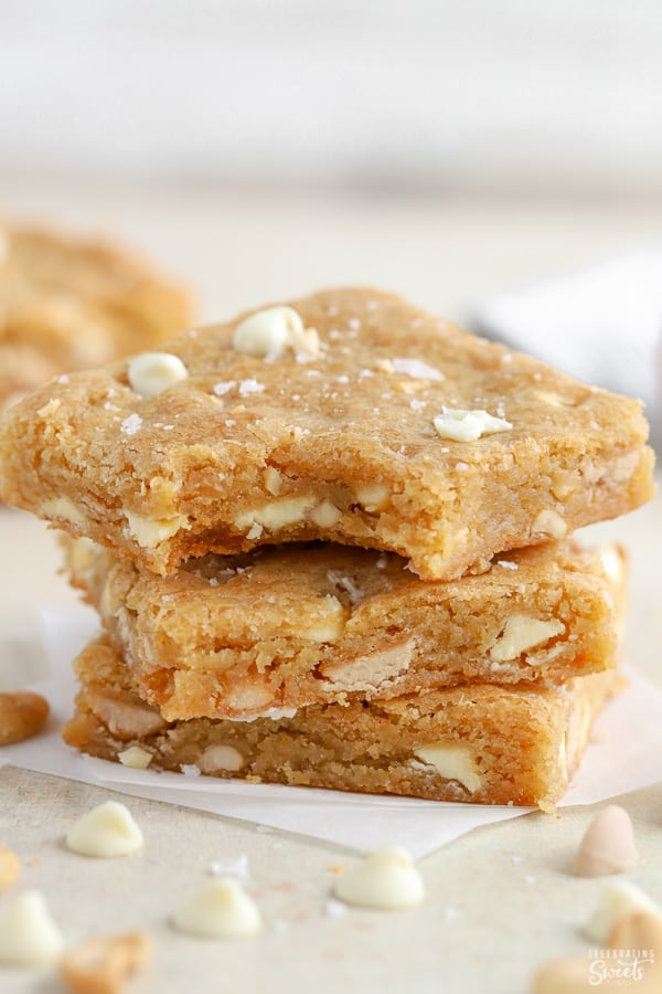 Stack of three blondie bars on parchment paper.
