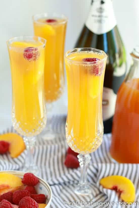 Three mimosas in champagne glasses garnished with a raspberry.