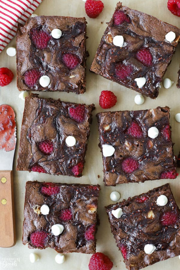 Raspberry brownies on a piece of brown parchment paper.