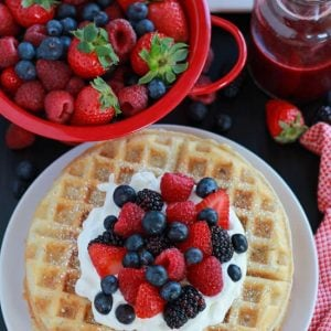White plate with waffles, berries, and whipped cream.