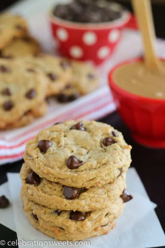 Stack of Peanut Butter Cookies with a Bowl of Peanut Butter and Cup of Chocolate Chips in the Background.