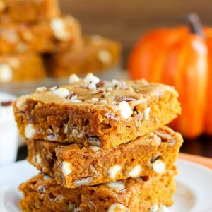 Stack of pumpkin bars on a white plate.