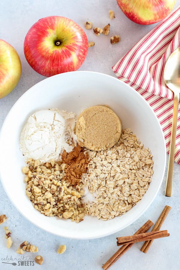 Flour, oats, brown sugar, nuts in a large white bowl. Filling for baked apples.