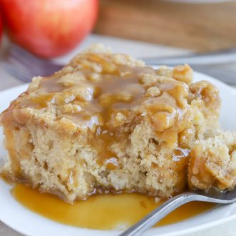A slice of apple cake on a white plate topped with caramel sauce.