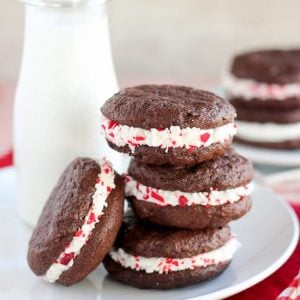 Stack of peppermint sandwich cookies with milk in the background.